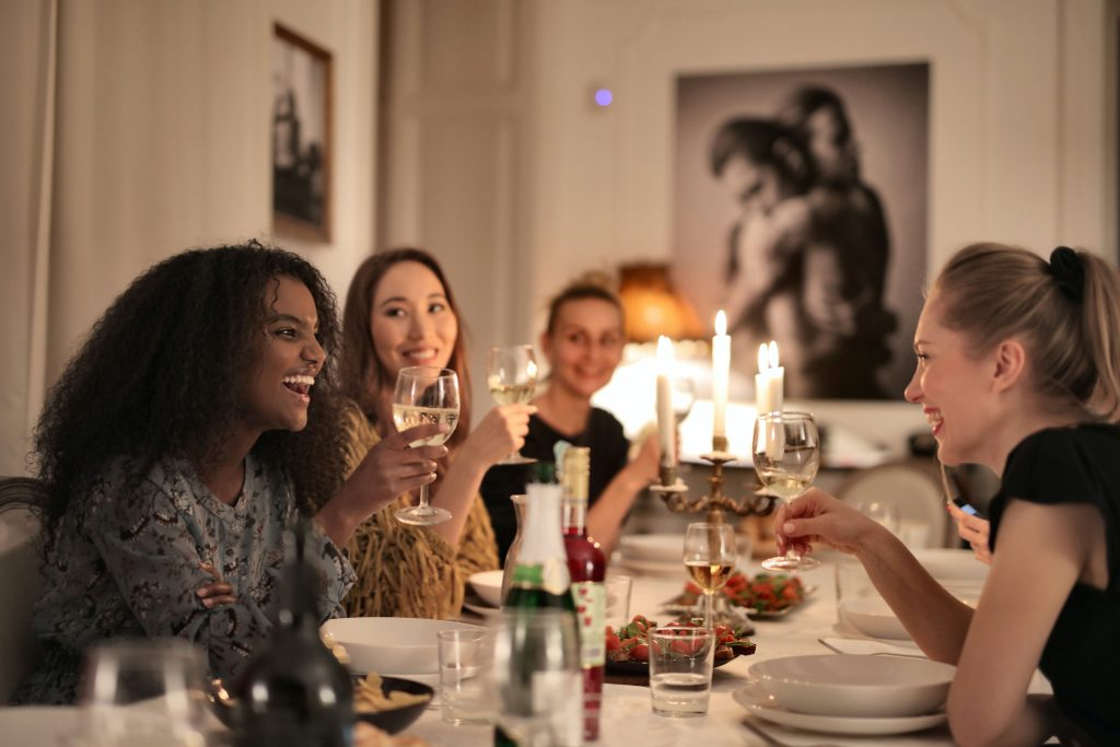 A group of friends at a dinner table enjoying wine and laughing, basking in each-other's company, choosing to not spend their time with draining people.