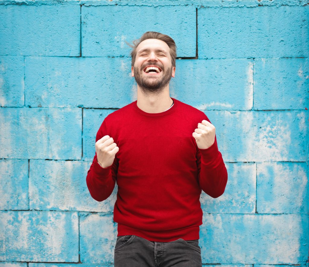young man in red jumper with fists pumped in air, symbolising the excitement of goal setting