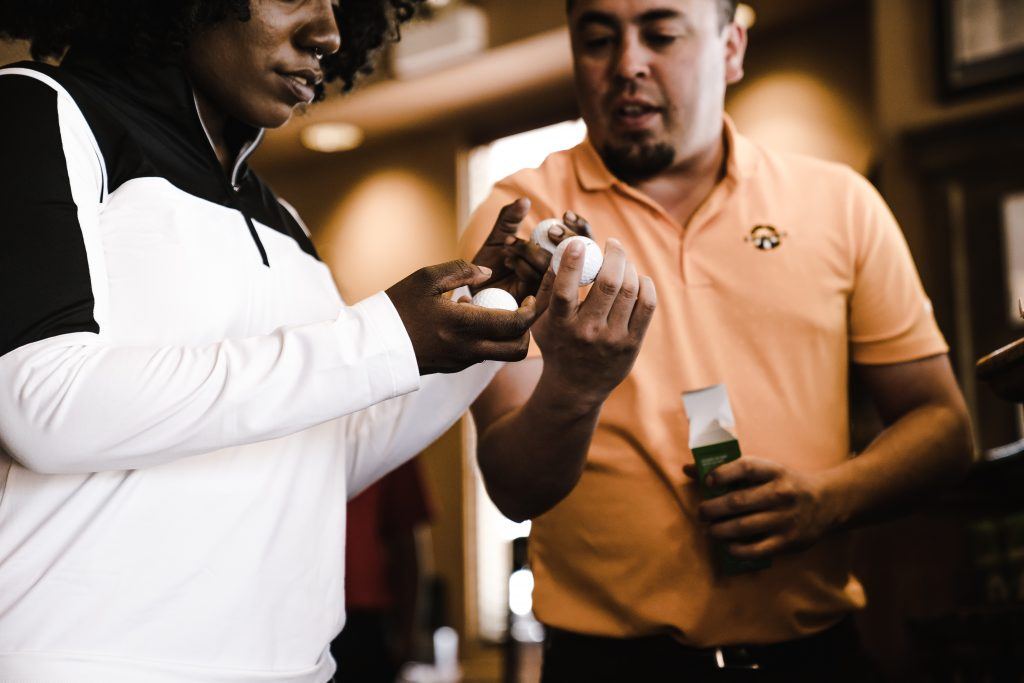 When entrepreneurs start a business, there are many options. Here, a man deals with a customer in his business - selling golf products.