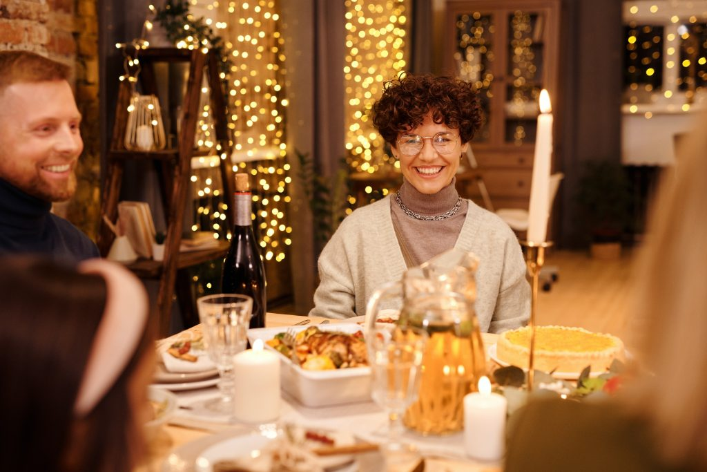 Woman at a party, sitting at a dinner table, happy and content