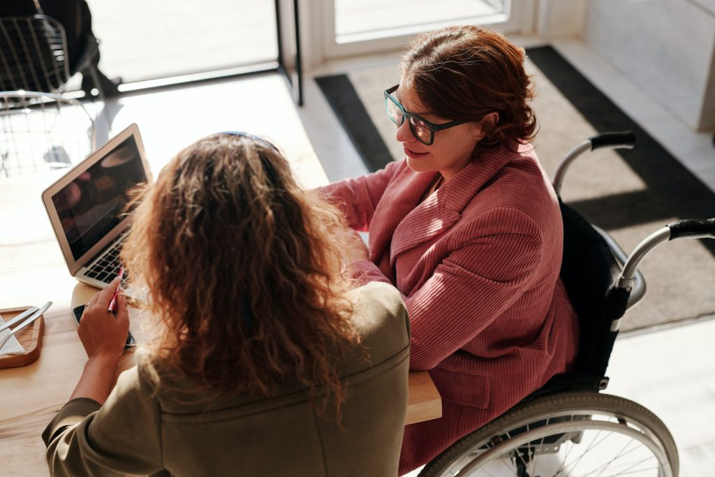 two women sitting together at a desk discussing how to get a pay rise - a boss and employee in discussion