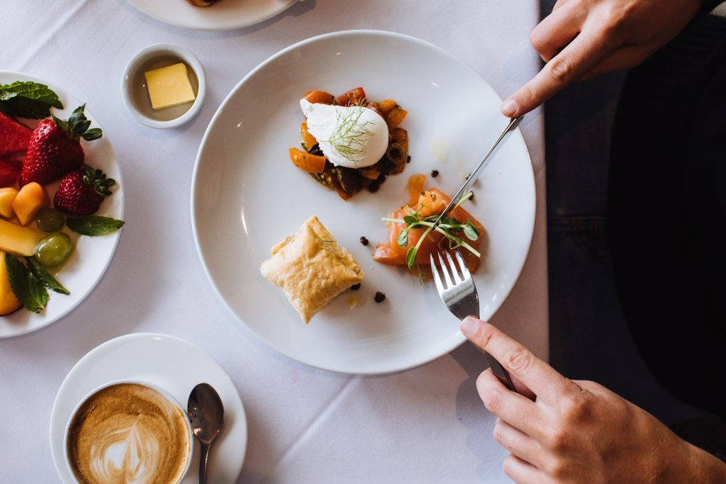 food on a plate, restaurant quality - with somebody sampling it, encouraging initial sales in the restaurant's business