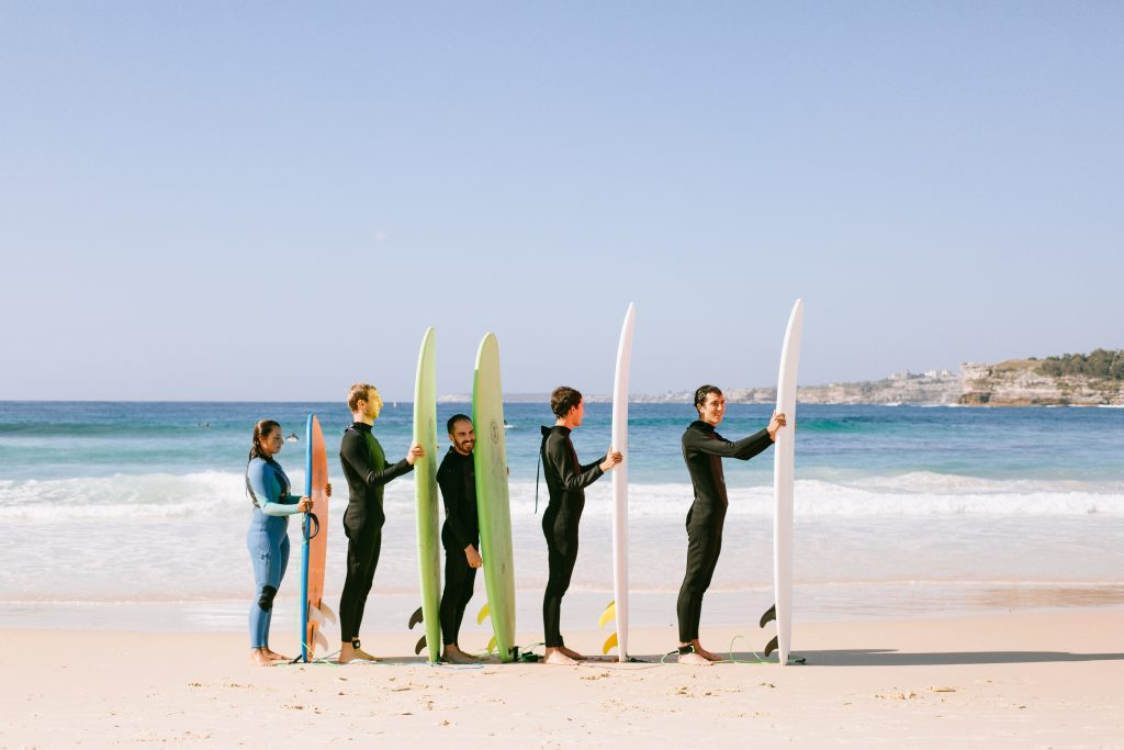 people with surfboards standing on a beach signifying business growth