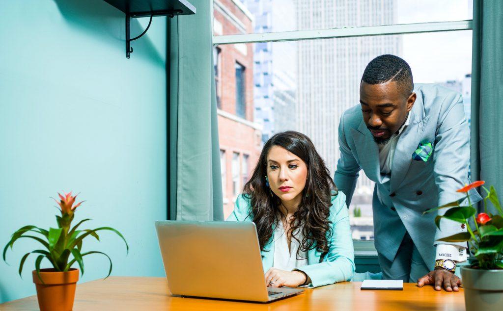 man behind woman at laptop, coaching her