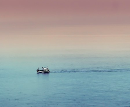 A lone fishing trawler returns home at sunrise with the nights catch