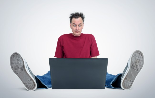 Programmer sitting on the floor in front of a laptop