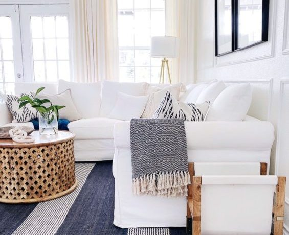 A white slipcovered sectional sofa and striped rug add a touch of relaxed summer style to our living room - jane at home #decor #design #homedecorideas #style