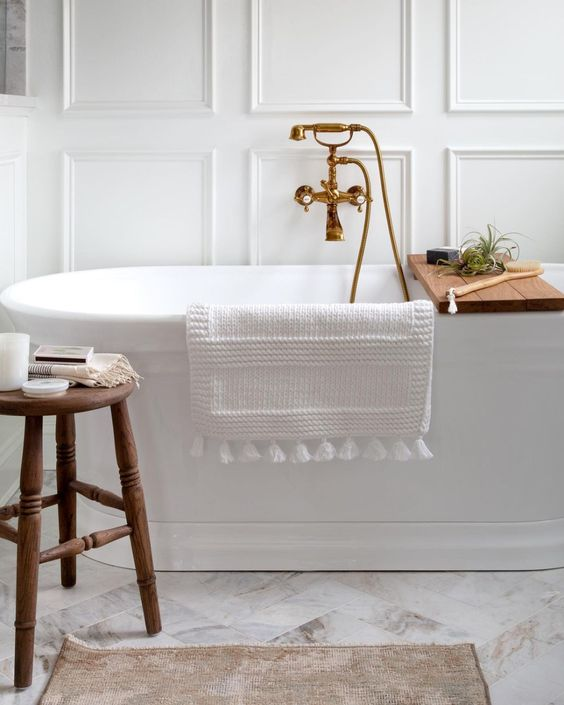 Beautiful all white bathroom design with marble tile floor, freestanding tub and accent wall trim - bathroom remodel - bathroom ideas - bathroom design