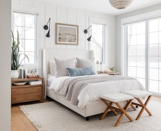 A beautiful lake house master bedroom design with layered bedding and modern coastal decor - lily pad cottage