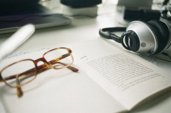 headphones, a book, and reading glasses
