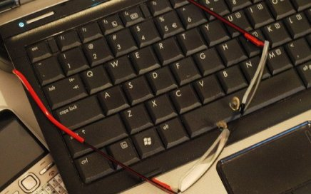 A black computer keyboard with red-framed glasses on top.