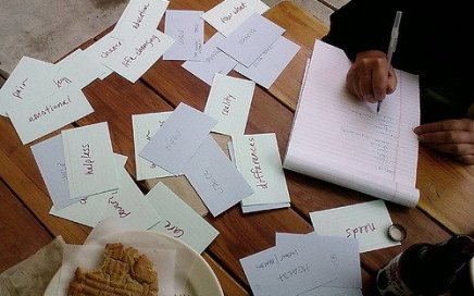 A person outlining ideas among various flashcards listing goals