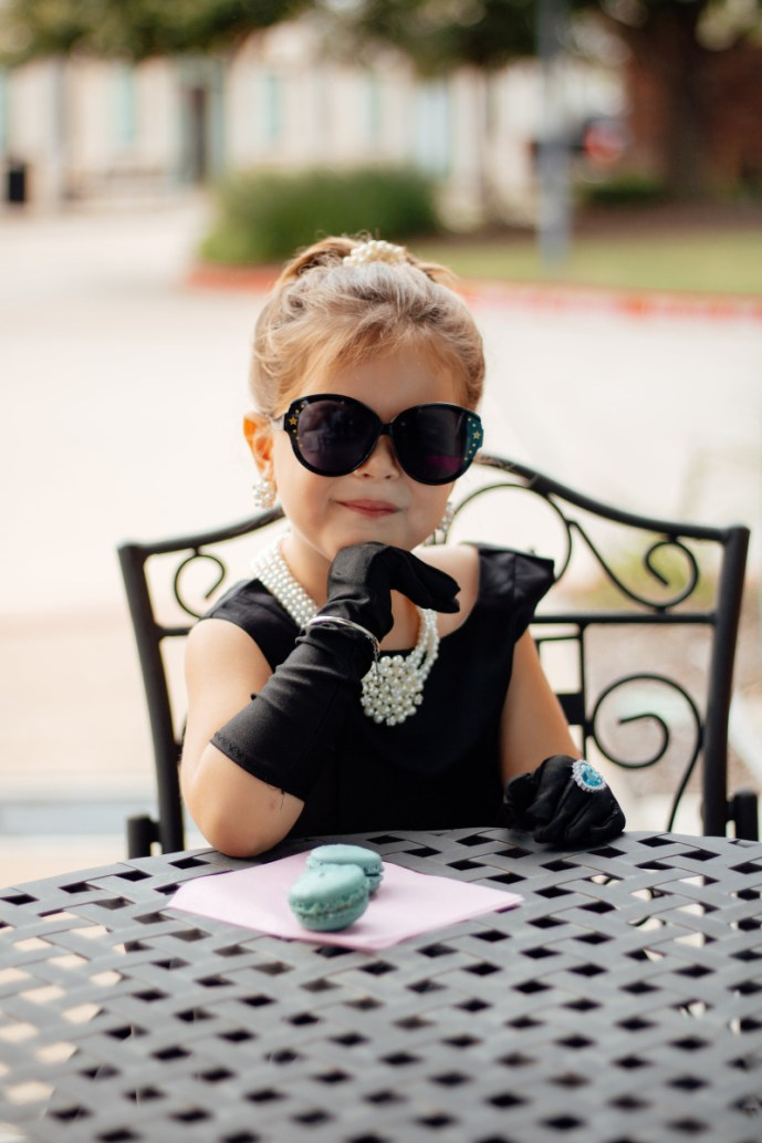 Girl sitting at table in Breakfast At Tiffany's costume