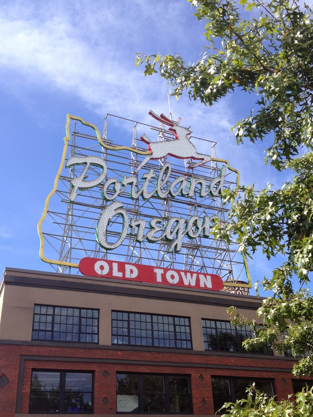 Portland Oregon Old Town sign blue skies packing for business travel work trip