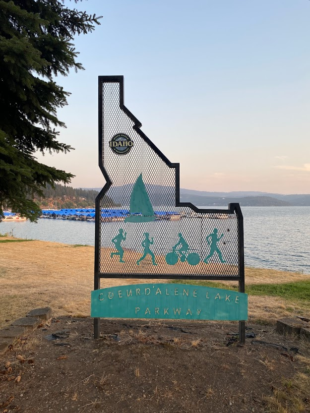 Coeur d'Alene Parkway State Park sign in front of the lake at dusk