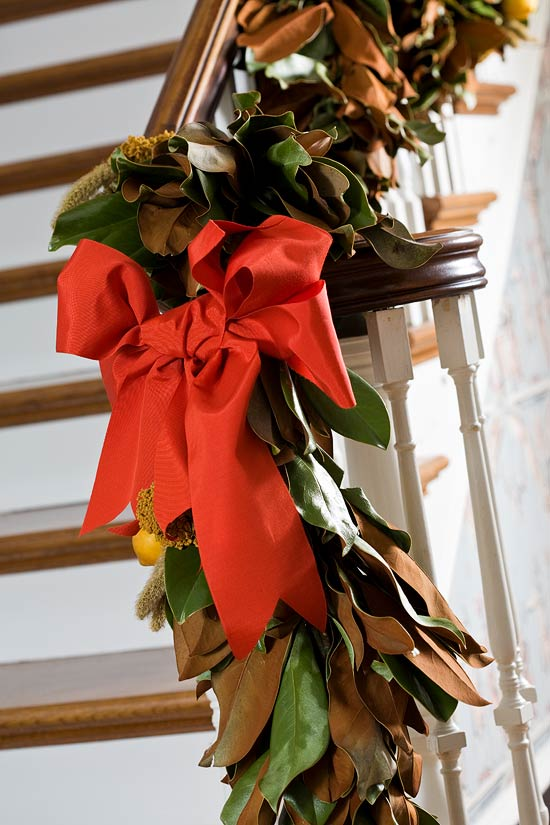 Decorating with Magnolia   Janet Brown Interiors    In the entry hall  a magnolia garland winding up the balustrade is adorned  with lemons and coral ribbon     Jon and Jennifer Abramczyk s 1928  Wilmington