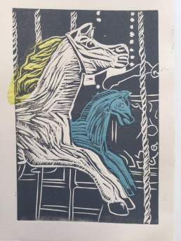 Carousel horse woodcut on Somerset Velvet paper in a dark grey ink with blue Korean paper and yellow tissue.
