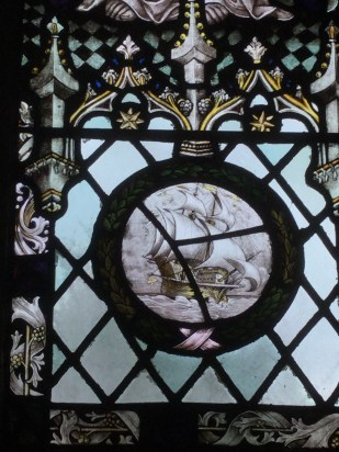 Detail of stained glass showing a historical warship under sail.