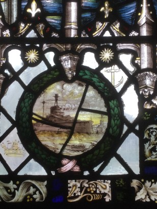 Detail of stained glass window showing a ship in a battle at sea.