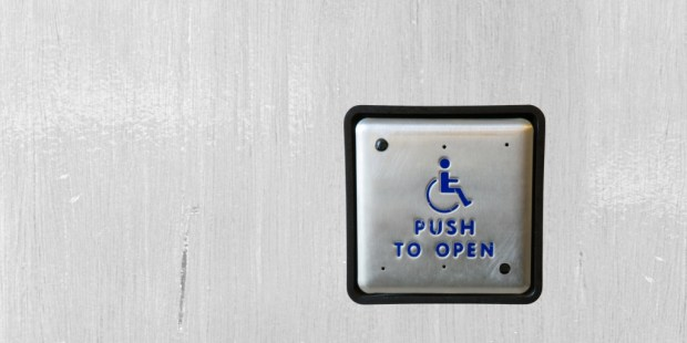 A photo of a button for people in wheelchairs to open a door