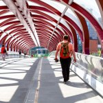 A man walking over a red bridge in Calgary - symbolizing Internet of Things advancement