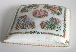 This is a pincushion design that was featured in Inspirations magazine. The pincushion is stitched in various embroidery stitches, and measures nearly five inches square