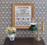 A doll's house scale 'Count Your Blessings' sampler on 32 count evenweave, available as a kit from www.janetgranger.co.uk