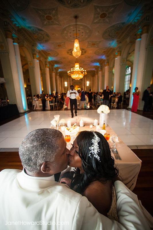 Bride and Groom kiss during dinner at Biltmore Ballrooms wedding