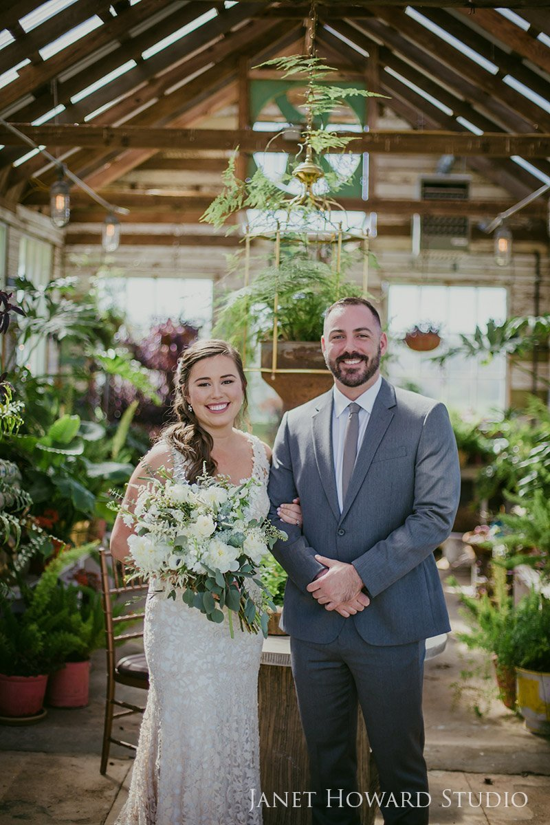 bride and groom portrait in greenhouse