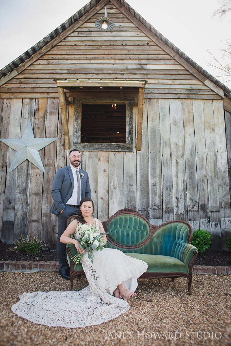 Bride and groom with barn at West Milford Farm