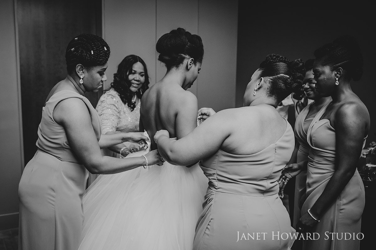 bridesmaids helping bride getting dressed