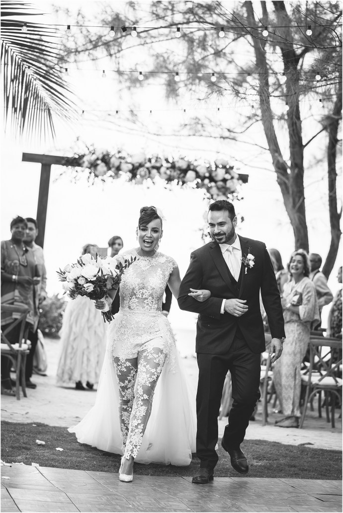 black and white, bride and groom walking down the aisle