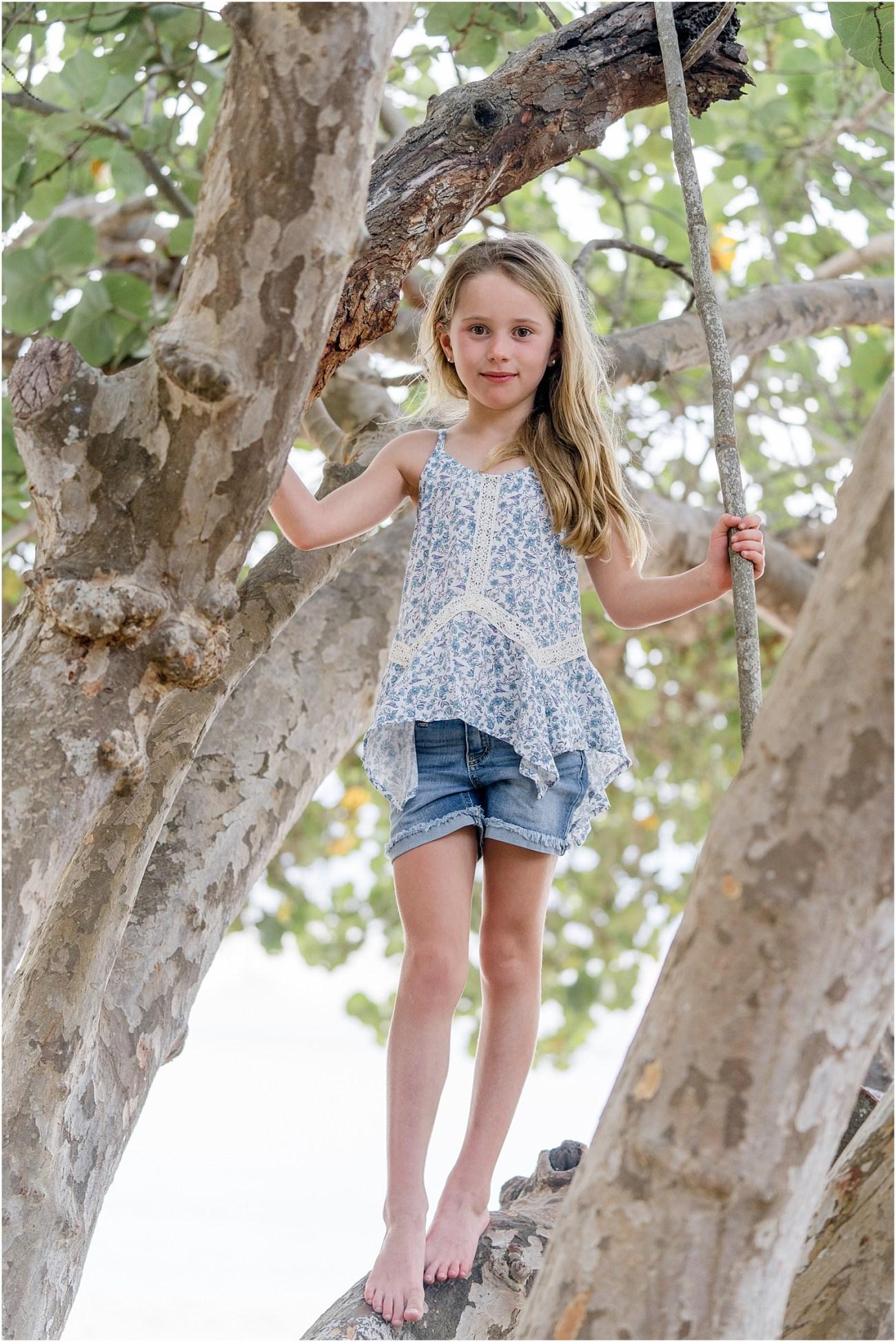 little girl climbing on tree