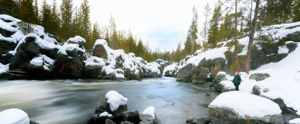 Firehole River in snow with 2 photographers standing on the edge.  Wter Blur.