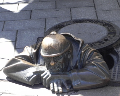 Brass statue of a worker peeking out of a manhole