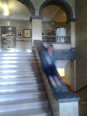 Blurred image of Janet sliding down the banister