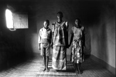 Rwanda : Flora Mukampore. For over a month Flora lay unconscious under dead bodies and maggots until some children found her. Here, she stands in between two of her dead sister's children. 17 members of her family were killed in the genocide