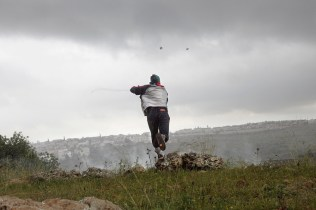 Ni'lin, West Bank, Palestine - March 26, 2010: A man uses a slingshot to hurl a rock at the Israeli military during the friday demonstrations that take place at the Israeli separation barrier in the village. ( Photo by Philip Cheung )