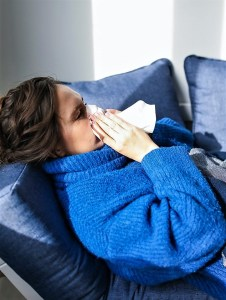 Woman blowing nose on blue couch