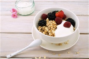 white bowl of plain yogurt with berries and oats