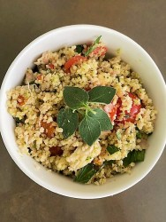 white bowl of couscous salad with fresh oregano leaves
