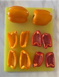 Whole yellow bell peppers with red and yellow quartered peppers on cutting board