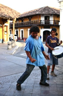 A man dances to the music of a group of street kids