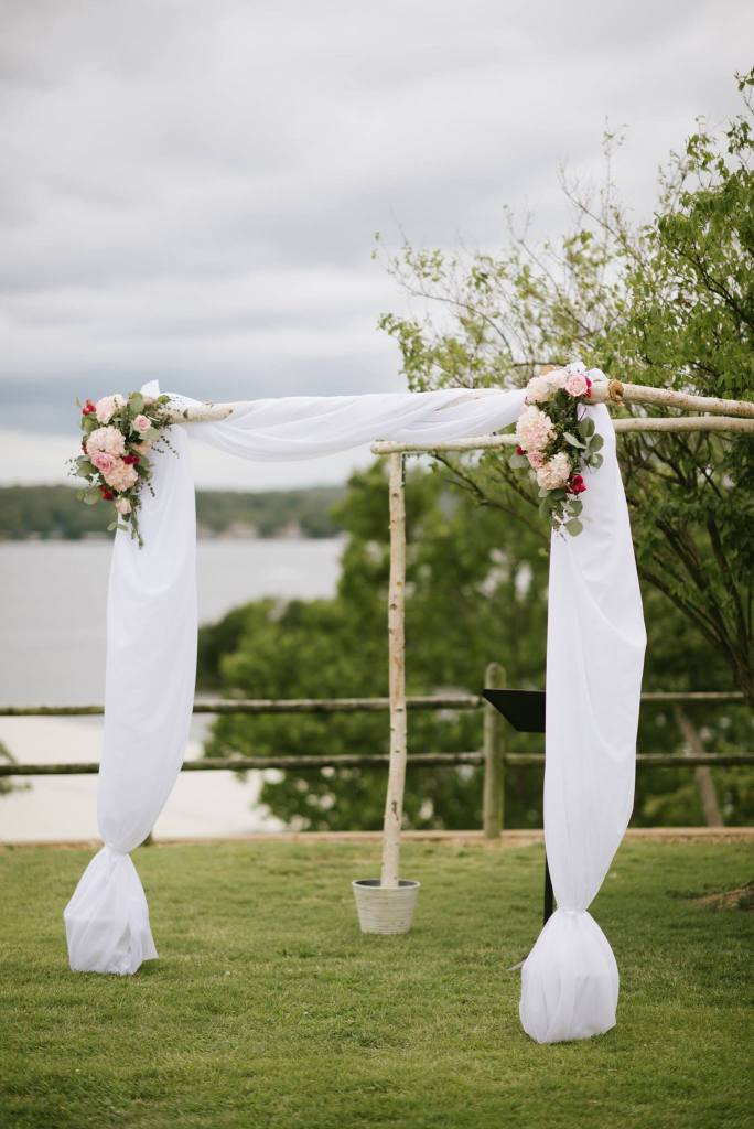 Arbor, wedding flowers, ceremony flowers, fresh flowers, arbor rental, lake wedding, lake of the ozarks, wedding flowers, white fabric on arbor, birch arbor, rental, camdenton, lake ozark, osage beach, wedding flowers, janine's flowers,