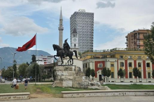 Plac Skanderberga. Widok na wszystko, co się da: pomnik bohatera przy łopocie narodowej flagi, stary meczet i zabytkowa wieża zegarowa, nowoczesny, pięciogwiazdkowy Hotel Plaza i jeszcze góry.