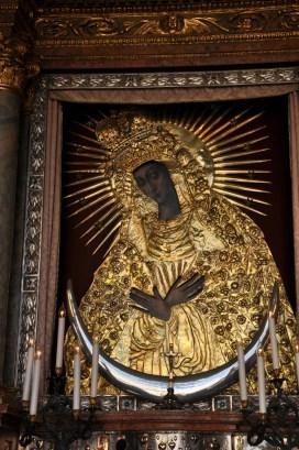 Deski dębowe, technika temperowa, podkład klejowo-kredowy. Wymiary 200 na 165 cm. Autor raczej nieznany. Prawdopodobnie XVIIw. Według legendy Matka Boska ma rysy Barbary Radziwiłłówny. Postać Maryi zakrywa złota sukienka. Pod sukienką Madonna ubrana jest w czerwoną tunikę, białą chustę na głowie i zielonkawo-błękitny płaszcz zarzucony na głowę i ramiona. Matka Boska Miłosierdzia - Matka Boska Ostrobramska.