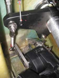 Etwas schwierig zu erkennen: Das große schwarze Teil unten ist der Motor des Autopiloten, oben sieht man die Mechanik, mit der die Kraft auf den Ruderquadranten übertragen wird. Der Ruderquadrant ist das große schwarze Teil oben. Rechts im Bild, das silberne Rohr, ist der Ruderschaft. In der Folge des Bruchs der Schweißnaht hat die Hebelmechanik des Autopiloten die Ruderanlage teilweise blockiert. Als Folgeschaden sind die Schrauben, die die zwei Teile des Ruderquadranten auf dem Ruderschaft gehalten haben, aus dem Aluminium herausgedrückt worden. Dafür mußten dann neue Ersatzteile aus Deutschland kommen.