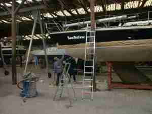 Zwei Leute der Werft streichen die erste Schicht GelShield auf den Rumpf.