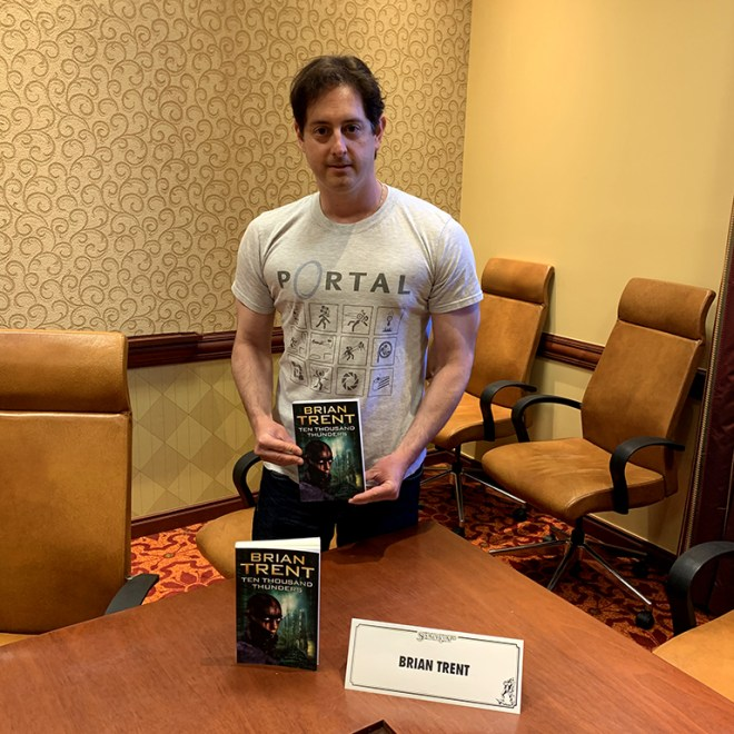 """Author Brian Trent poses with a copy of his book """"Ten Thousand Thunders,"""" before reading an excerpt for it."""