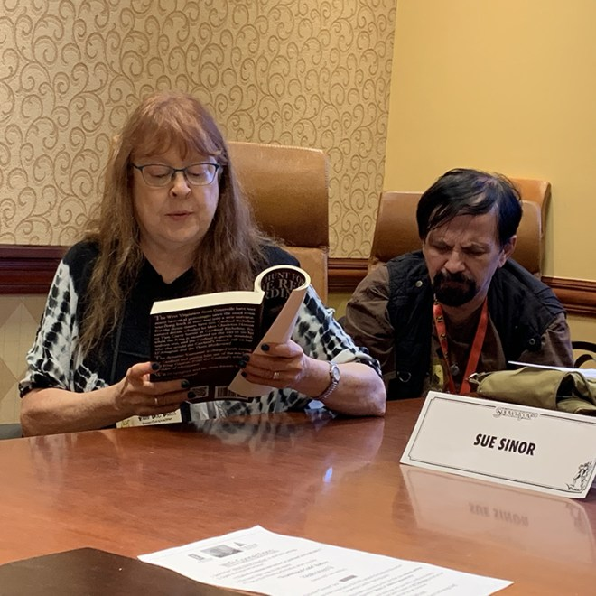 """Susan P. Sinor reads from her alternate history novel, """"The Hunt for the Red Cardinal,"""" while her co-author-husband Bradley H. Sinor listens."""